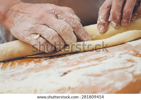 Close up photo of baker kneading dough with a rolling pin. Retro styled imagery. Grain added - stock photo