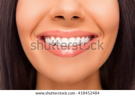 Close up photo of beaming woman's smile and healthy teeth - stock photo