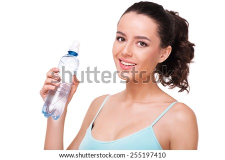 Close up photo of beautiful sporty woman holding a bottle of water, isolated on white background - stock photo