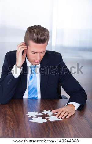 Close-up Photo Of Businessman Connecting Jigsaw Puzzle - stock photo