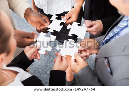 Close-up Photo Of Businesspeople Holding Jigsaw Puzzle - stock photo