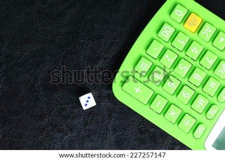 Close up photo of calculator and dice on black leather surface background focusing on calculator button