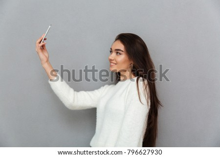 Close-up photo of charming brunette woman with long hair holding smartphone while taking selfie, isolated over gray background