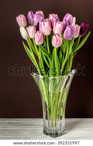 Close-up photo of colorful tulips in glass vase on brown background.