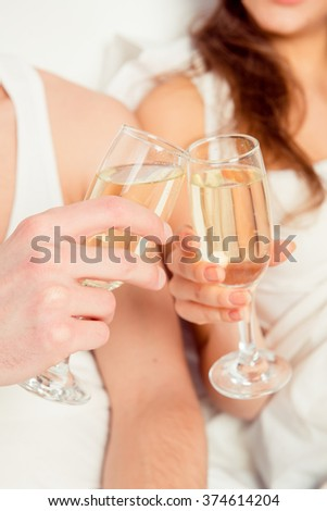 Close up photo of couple in love clinking glasses of champagne - stock photo