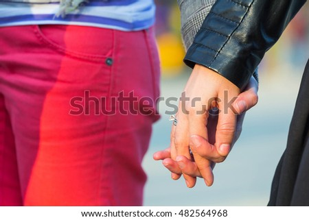 Close up photo of couple showing love by holding hands