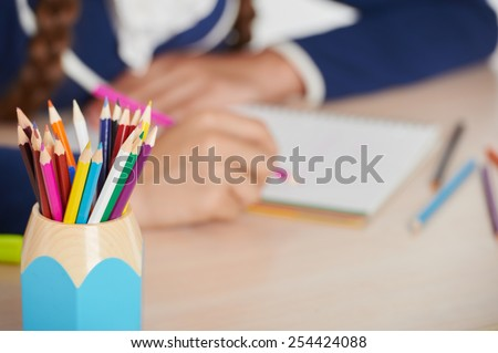 Close up photo of cup with pencils. Young school girl with pencil writing while sitting in school desk - stock photo