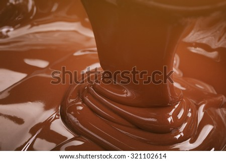 close up photo of dark chocolate flow, premium chocolate - stock photo