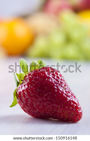 Close up photo of edible fruits - a strawberries with other full color fruits in the background on a solid  bright blue wooden table