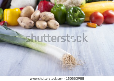 Close up photo of edible vegetables - a leek with some vegetables in the background on a solid  bright blue wooden table