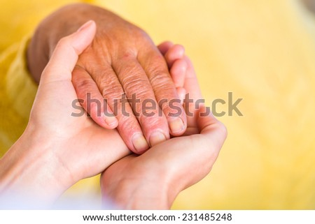 Close up photo of elderly woman hand hold by young carer hand - stock photo