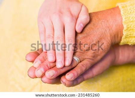 Close up photo of elderly woman hands touched by young carer hand - stock photo