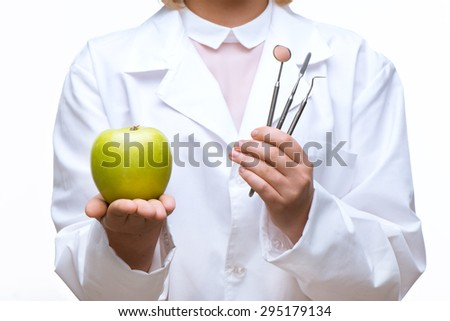 Close up photo of female dentist. There are dental instruments and green apple in her hands - stock photo