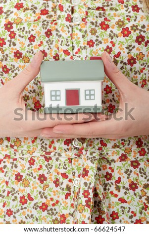 Close up photo of female hands holding house model - stock photo