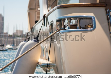 Close-up photo of fenders hanging on the side of a white yacht which is in the port on a sunny day with other ship masts in the background
