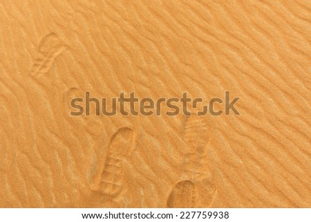Close-up photo of footprints on the sand of a desert in the United Arab Emirates - stock photo