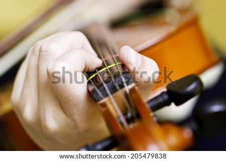 close up photo of hands holding a violin neck and strings - stock photo