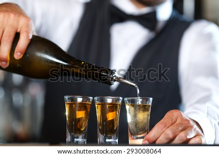 Close up photo of hands of a bartender pouring some shots into small glasses on a wooden counter - stock photo