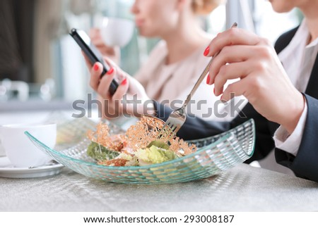 Close up photo of hands on a woman holding a fork eating a salad and a mobile phone reading some important emails, in a restaurant during business lunch selective focus