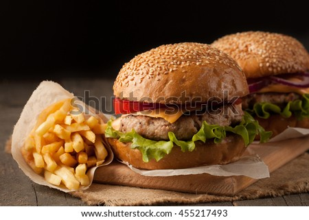 Close-up photo of home made hamburger of beef, onion, tomato, lettuce, cheese and spices with a glass of light beer. Fresh burger closeup on wooden rustic table with potato fries and chips.
