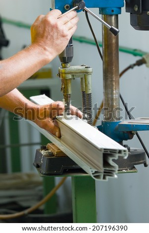 Close up photo of joiner's worker hands doing some job on big metalworking machine. Selective focus. Shallow DOF. - stock photo