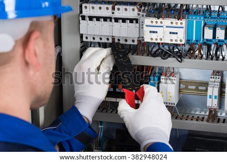 Close-up Photo Of Male Electrician Repairing Fusebox - stock photo