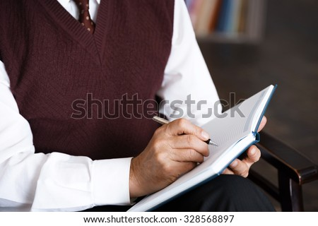Close up photo of male psychologist. Psychologist making notes in psychologist office