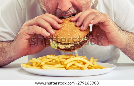 close up photo of man eating burger and french fries - stock photo