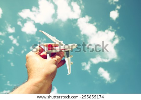 close up photo of man's hand holding toy airplane against blue sky with clouds - stock photo