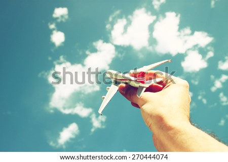 close up photo of man's hand holding toy airplane against blue sky with clouds. filtered image  - stock photo