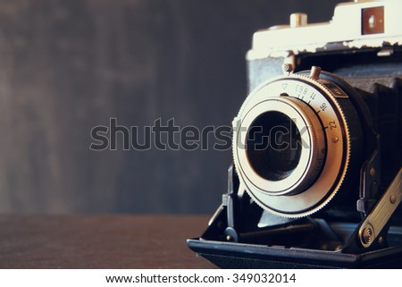 close up photo of old vintage camera lens over wooden table. selective focus  - stock photo
