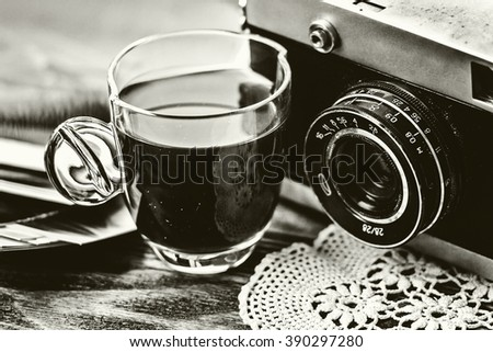 Close up photo of old, vintage camera lens with cap of coffee and black and white photos over wooden table. Nostalgic holidays background. Memories concept. BW image. Selective focus - stock photo