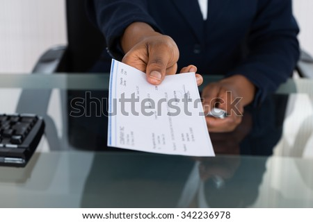 Close-up Photo Of Person's Hand Giving Cheque - stock photo