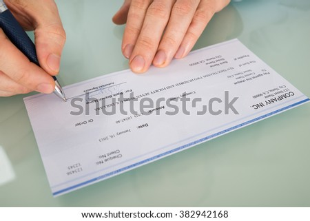 Close-up Photo Of Person's Hand Signing Cheque - stock photo