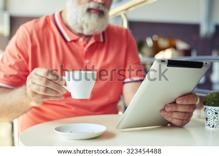 close-up photo of senior bearded man with cup of coffee and tablet pc in cafe