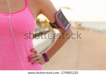 Close-up photo of smartphone holder on woman's arm - stock photo