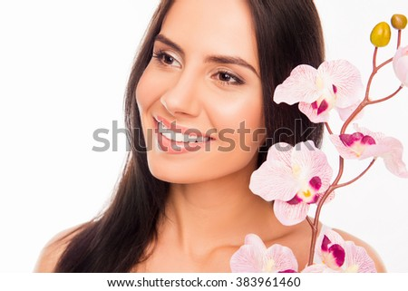 Close up photo of smiling brunette holding orchid near her face