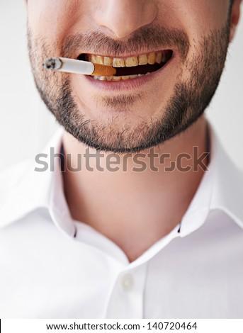 close-up photo of smoking man with dirty yellow teeth - stock photo