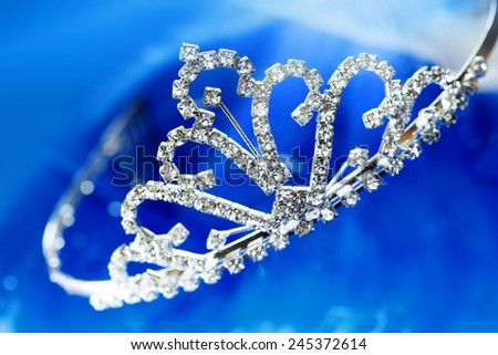 Close-up photo of the silver diadem with diamonds on a blue background with bokeh - stock photo