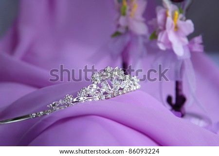 Close-up photo of the silver or platinum (white gold) diadem with diamonds on a lilac background. In the background are visible flower decorations