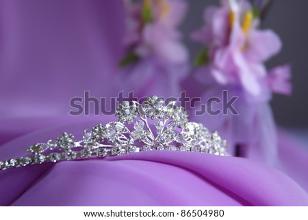 Close-up photo of the silver or platinum (white gold) diadem with diamonds on a lilac background. In the background is purple fabric and decoration of flowers. Tiara for the bride.