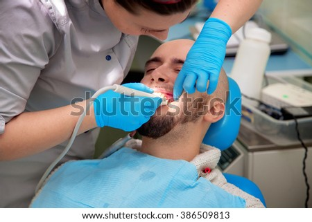 close up photo of Woman dentist checks the teeth of her patient in the dental office. Medicine, dentist, health and stomatology concept