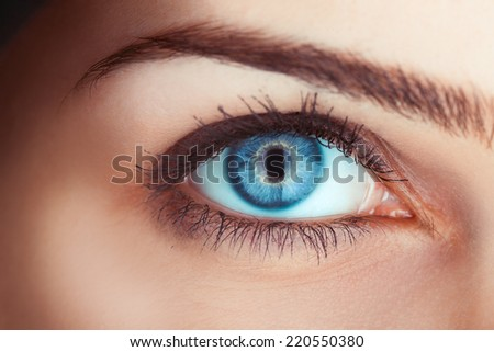 Close up photo of woman's blue eye in studio - stock photo