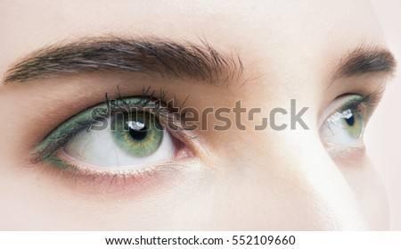 Close up photo of woman's green eye in studio