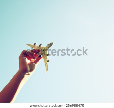 close up photo of woman's hand holding toy airplane against blue sky . image is retro filtered  - stock photo