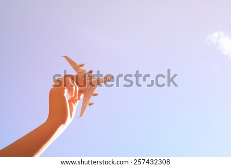 close up photo of woman's hand holding toy airplane against blue sky with clouds  - stock photo