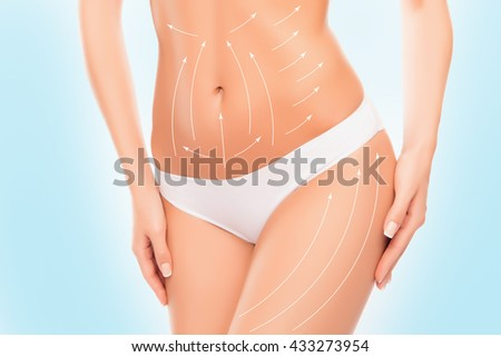 Close up photo of woman touching her  hip with drawing arrows on it - stock photo