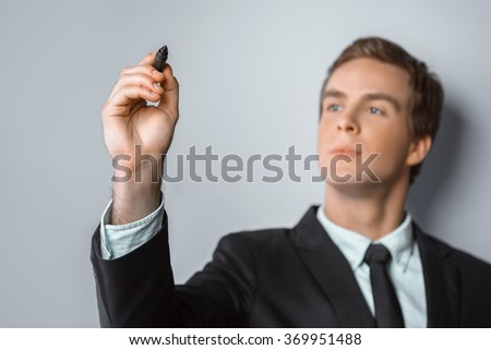 Close up photo of young attractive businessman. Businessman writing with felt pen on screen