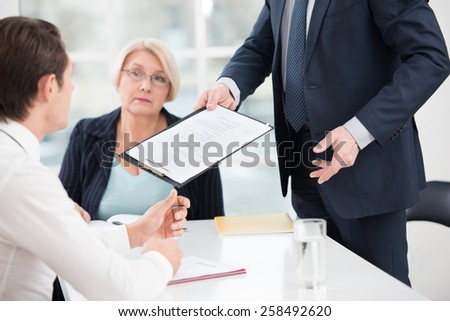Close up photo of young man having an interview or business meeting with employers. Director giving prospective employee to complete a questionnaire. Office interior with big window - stock photo