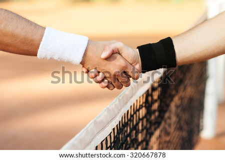 Close up photo of young men on tennis court. Men playing tennis. Men shaking hands above net before game - stock photo